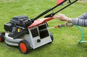 Entretien d une tondeuse au début du printemps avant la première tonte de la pelouse. Nettoyage au jet d eau.