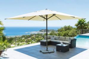 Le parasol occupe l'espace et ombrage avec élégance le salon de jardin