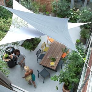 Décorer sa terrasse : Voiles d'ombrage, table en bois et jeu de couleur avec les chaises