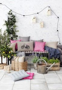 Éléments de déco : Canapé, coussins, plantes, panier, arrosoir, guirlande