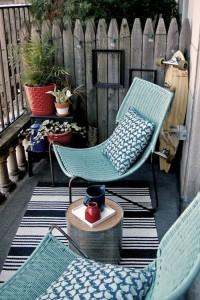Éléments de déco : fauteuils, coussins, tapis, pot de fleur, petite table, cadres noirs